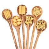 Pasta Types. Pasta selection of penne, gnocci, rigatoni, casarecce, fiorelli and algar in wooden spoons over white background Stock Photo