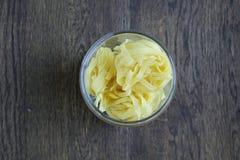 Pasta in una latta sulla tavola di legno immagine stock