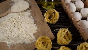 Pasta, uova, petrolio, pomodori, aglio e farina su fondo di legno archivi video