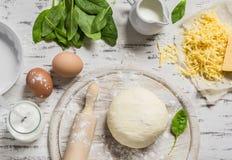 Pasta, uova, spinaci freschi, formaggio - ingredienti crudi per preparare torta con spinaci, formaggio ed uovo su un fondo di leg Fotografia Stock