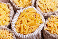 Pasta variety in burlap bags - closeup, top view Stock Photos
