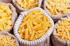 Pasta variety in burlap bags - closeup, top view Stock Photos