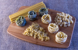 Pasta Variety Still Life. On wooden cutting board and burlap background stock image