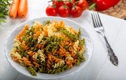 Pasta variopinta di rutini con le verdure come come fondo fotografia stock
