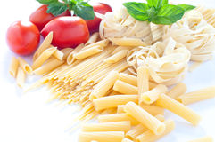 Pasta of various sizes with tomato and basil Stock Images