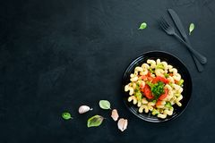 Pasta with vegetables. On a black background. Top view. Free space for your text stock image