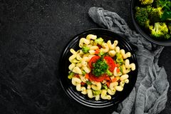 Pasta with vegetables. On a black background. Top view. Free space for your text royalty free stock photo