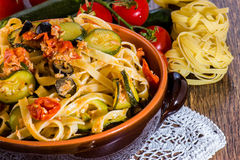 Pasta with vegetables in ceramic clay pot Stock Photos