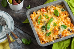 Pasta and vegetables gratin. Oven-baked pasta with colourful olive, peppers and tomatoes. Pasta and vegetables gratin in baking dish stock photography