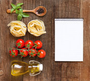 Pasta, vegetables, herbs and notebook Royalty Free Stock Photos