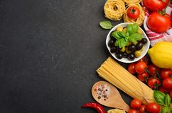Pasta, vegetables, herbs and spices for Italian food on black background. Pasta, vegetables, herbs and spices for Italian food on black background, top view stock image