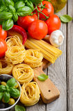 Pasta, vegetables, herbs and spices for Italian food on white wooden background Royalty Free Stock Photos