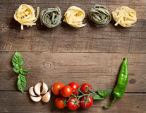 Pasta, vegetables and herbs on wood Royalty Free Stock Images