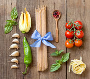 Pasta, vegetables and herbs on wood Stock Images