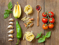 Pasta, vegetables and herbs on wood Stock Image