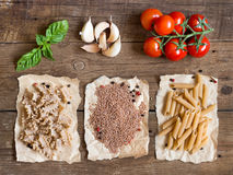 Pasta, vegetables and herbs on wood Royalty Free Stock Photos