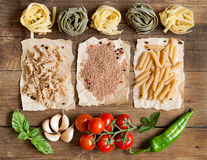 Pasta, vegetables and herbs on wood Stock Photo