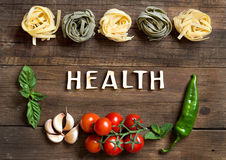 Pasta, vegetables and herbs on wood. En background stock image