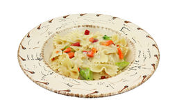 Pasta with vegetables in southwestern style bowl. Serving of pasta with vegetables and thin sauce in a southwestern style bowl on a white background Royalty Free Stock Image