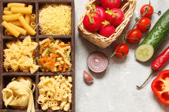 Pasta with vegetables, spices and herbs in wooden cells Stock Image