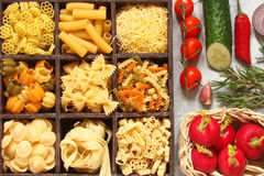 Pasta with vegetables, spices and herbs in wooden cells Stock Photos