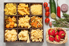 Pasta with vegetables, spices and herbs in wooden cells Royalty Free Stock Photo