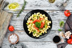 Pasta with vegetables. On a white wooden background. Top view. Free space for your text royalty free stock photography