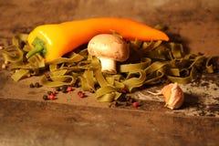 Pasta verde con gli ingredienti su fondo di pietra immagini stock