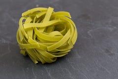 Pasta verde cruda di tagliatelle su un piatto dell'ardesia Fotografie Stock