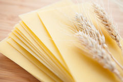 Pasta and wheat ears on a wooden surface Royalty Free Stock Image