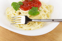 Pasta in white glass plate with tomato ketchup and parsley Stock Photo