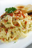 Pasta with white sauce. Sprinkled with ground pork top with basil and toasted sandwich Stock Image