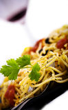 Pasta and wine 2. Black plate with pasta and glass of wine in background Royalty Free Stock Images