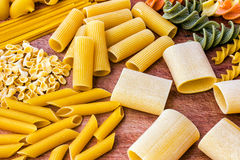 Pasta on Wooden Board. Raw Food. Closeup of different types of pasta on a wooden cutting board Stock Image