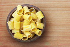 Pasta in wooden bowl Stock Photos