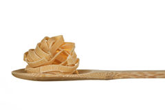 Pasta on wooden spoon. Raw tagliatelle on wooden tablespoon against white background stock images