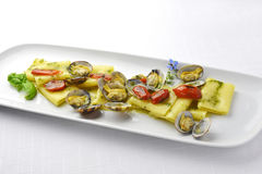 PastamaträttPaccheri makaroni med musslor grillade tomater och basilika Arkivfoton