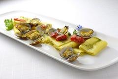 PastamaträttPaccheri makaroni med musslor grillade tomater och basilika Arkivbild