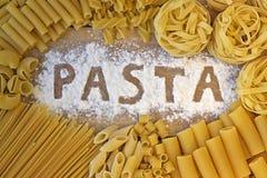 Pastaord med wood bakgrund Arkivfoton