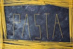 Pastaordet på den mörka bakgrunden arkivbild