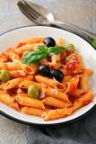 PastaPenne closeup i tomatsås med oliv och basilika på en sl Arkivfoto