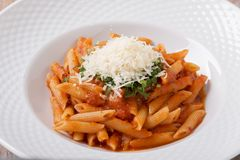 Pastapenne med sås för tomaten för parmesanost gör grön arkivbilder