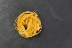Pastas amarillas crudas de los tallarines en una placa de la pizarra Fotografía de archivo libre de regalías