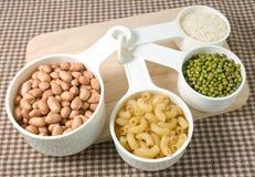 Pastas, arroz, cacahuetes y habas de Mung en cucharas dosificadoras Foto de archivo libre de regalías