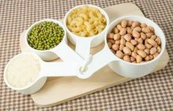 Pastas, arroz, cacahuetes y habas de Mung en tazas de medición Imágenes de archivo libres de regalías
