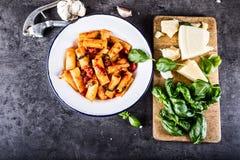 Pastas Cocina del italiano y de Mediterrannean Las pastas Rigatoni con albahaca de la salsa de tomate salen del ajo y del queso p Foto de archivo