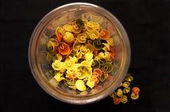 Pastas coloreadas en un tarro transparente Imagen de archivo