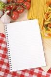 Pastas con el libro en blanco de la receta y el mantel rojo del control Foto de archivo