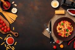 Pastas con el queso, salsa de tomate de cereza, pimienta, ajo, cúrcuma en fondo oxidado imagen de archivo libre de regalías