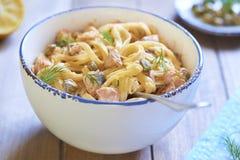 Pastas con el salmón ahumado y las alcaparras en salsa cremosa Imagen de archivo